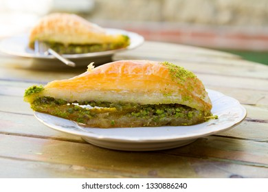 Havuc Dilim Turkish Baklava with pistachio and tea on wood table background.