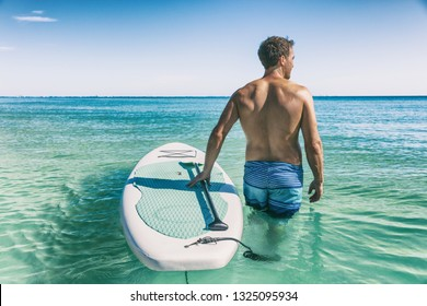 Hawaii beach fitness watersport man with SUP paddle board doing stand up paddle boarding in water.