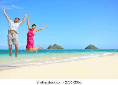 Hawaii beach Vacation. Happy couple tourists jumping. Young couple cheering for summer holidays showing success, happiness, and joy on Lanikai beach, Oahu, Hawaii, USA with Mokulua Islands.