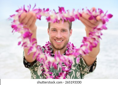 Hawaii Caucasian man with welcome Hawaiian lei. Male tourist portrait holding flower necklace giving it to the camera as a welcoming gesture for tourism in Hawaii. Travel vacation concept.