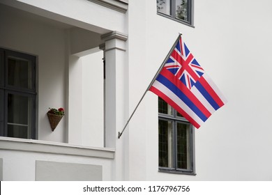 Hawaii flag. Hawaii state flag hanging on a pole in front of the house. State flag waving on a home displaying on a pole on a front door of a building. Flag raised at a full staff.