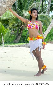 Hawaii Hula dancer on the beach, Exotic dancer relaxes on a tropical beach with palm trees.