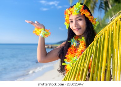 Hawaii hula dancers on the tropical sea beach invitation to an exotic tropical vacation  with a palm leaf shows blue sky.