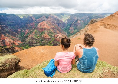 Hawaii Kauai nature hiking couple enjoying view of Waimea Canyon.Happy hikers healthy lifestyle outdoors looking at Waimea canyon. Young people taking a picnic break in nature in Kauai, Hawaii, USA.