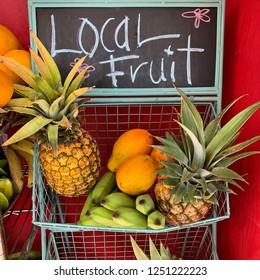 Hawaii: local fruit market with pineapples, bananas, and papayas