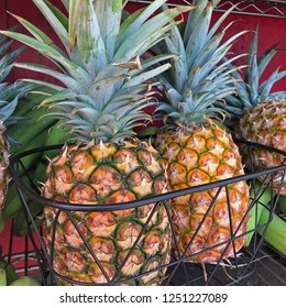 Hawaii: local fruit market with pineapples in basket alongside bananas