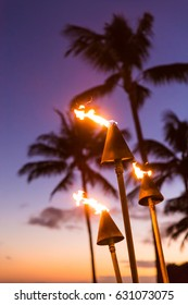 Hawaii sunset with lit tiki torches. Hawaiian icon, lights burning at dusk at beach resort or restaurants for outdoor lighting and decoration, cozy atmosphere.