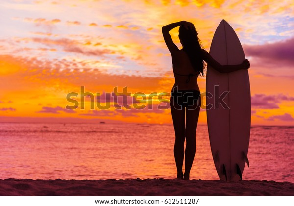 Hawaii surfer woman at sunset with surfboard on beach. Surf lifestyle.