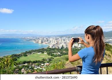 Hawaii tourist taking photo of Honolulu and Waikiki beach using smartphone camera. Woman tourist on hike visiting famous viewpoint lookout in Diamond Head State Monument and park, Oahu, Hawaii, USA.
