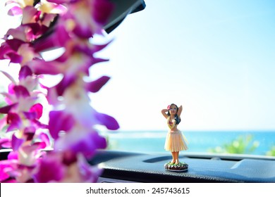 Hawaii travel car - Hula girl dancing on dashboard and lei during road trip.