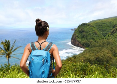 Hawaii travel nature hiker girl hiking in Pololu valley enjoying lookout view of mountains. Big island destination, woman tourist in Hawaii, USA.