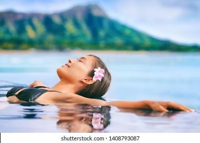 Hawaii vacation luxury resort travel Asian tourist girl relaxing in hotel infinity pool by Waikiki beach in Honolulu, Oahu. USA travel.