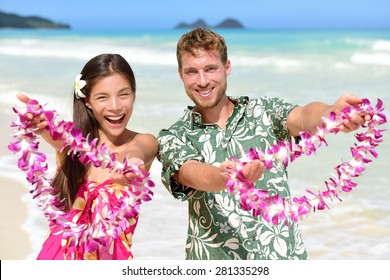 Hawaii welcome - Hawaiian people showing leis flower necklaces as a welcoming gesture for tourism. Travel holidays concept. Asian woman and Caucasian man on white sand beach in Aloha clothing.