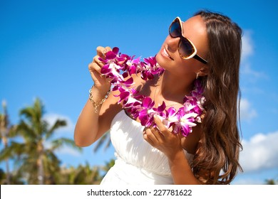 Hawaii woman with flower lei garland of pink orchids. Beautiful smiling woman in white dress. Welcoming Lei on the hawaiian island Honolulu.