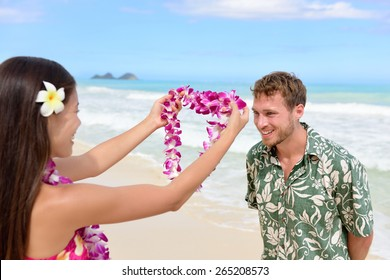 Hawaii woman giving lei garland of pink orchids welcoming tourist on Hawaiian beach. Portrait of a Polynesian culture tradition of giving a flower necklace to a guest as a welcome gesture.