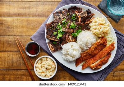 hawaiian bbq plate with mix of chicken katsu, korean kalbi beef short ribs, rice, and macaroni salad overhead composition