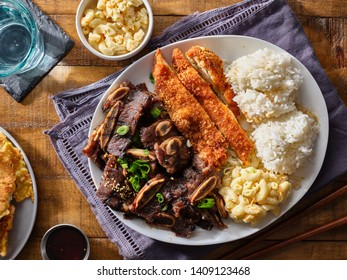 hawaiian bbq plate with mix of chicken katsu, korean kalbi beef short ribs, rice, and macaroni salad overhead composition