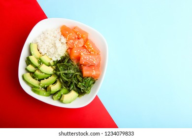Hawaiian dish poke bowl on blue and red background. Top view, copy space.