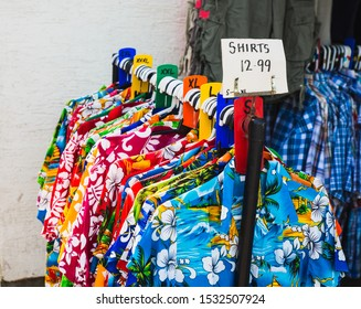 Hawaiian  floral shirts for sale in the small market on a clothes rail including a sign displaying they're on offer for £12.99. Funny fashion or used commonly for fancy dress clothes on holiday