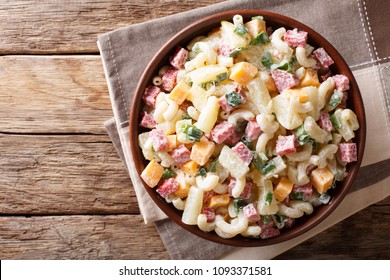 Hawaiian food: salad with pasta, ham, pineapple, onion, cheddar cheese with mayonnaise close-up in a bowl on the table. horizontal top view from above