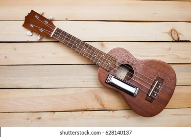 Hawaiian four-stringed ukulele guitar and iron harmonica on wooden background.