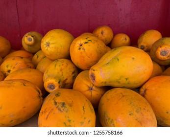 Hawaiian Fruit Market: pile of ripe papayas against a red wall