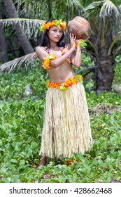 Hawaiian hula dancer carries a large coconut on a green background tropical nature.