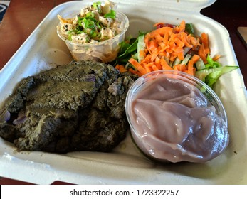 Hawaiian Lau Lau plate Served with Fresh/Day Old Poi in bowl, salad, Tofu poke in a cardboard container on a table.