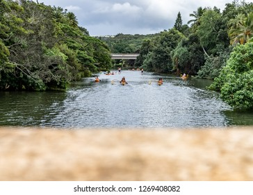 Hawaiian natives paddling on the Haleiwa River in a Outrigger canoe (Hawaiian canoe) passing under the Haleiwa Bridge on the island of Oahu in Hawaii on a cloudy day