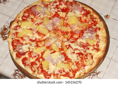 Hawaiian pizza on a round wooden plate