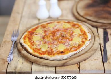 Hawaiian pizza with pineapple, ham and bacon.