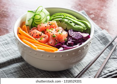 Hawaiian Poke Bowl with Sliced Salmon, Avocado, Cucumber, Purple Cabbage, and Carrots over Brown Rice with Chopsticks