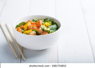 Hawaiian Poke salad with salmon, avocado and vegetables in a bowl on a white wooden rustic background with copy space. Good dieting. Healthy lunch