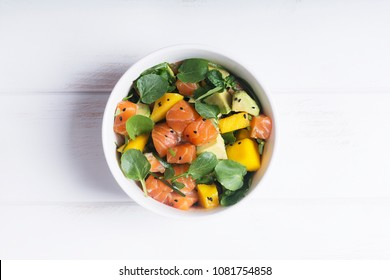 Hawaiian Poke salad with salmon, avocado and vegetables in a bowl on a rustic background. Good dieting. Healthy food
