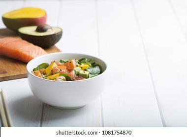 Hawaiian Poke salad with salmon, avocado and vegetables in a bowl on a white wooden rustic background with copy space. Good dieting. Healthy food