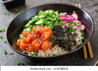 Hawaiian salmon fish poke bowl with rice, radish,cucumber, tomato, sesame seeds and seaweeds. Buddha bowl. Diet food
