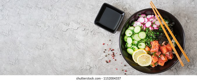 Hawaiian salmon fish poke bowl with rice, radish,cucumber, tomato, sesame seeds and seaweeds. Buddha bowl. Diet food. Top view. Flat lay. Banner