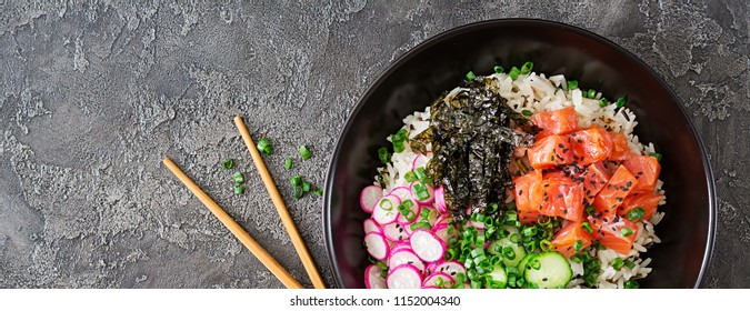 Hawaiian salmon fish poke bowl with rice, radish,cucumber, tomato, sesame seeds and seaweeds. Buddha bowl. Diet food. Top view. Flat lay. Banner