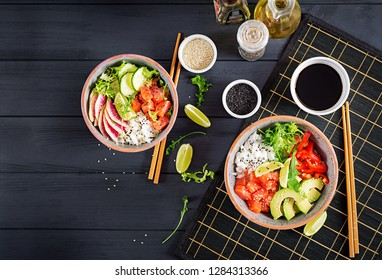 Hawaiian salmon fish poke bowl with rice, avocado, paprika, cucumber, radish, sesame seeds and lime. Buddha bowl. Diet food. Top view