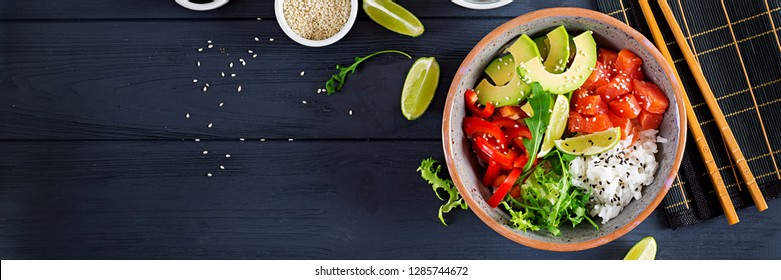 Hawaiian salmon fish poke bowl with rice, avocado, paprika, sesame seeds and lime. Buddha bowl. Diet food. Banner. Top view