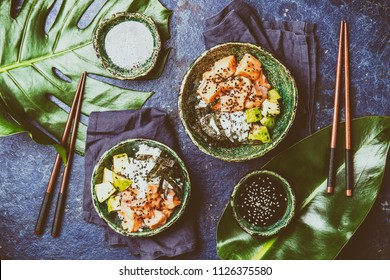 Hawaiian salmon poke poce with avocado, rice and sesamo served in bowls on tropical leaves. Sushi bowl. Turquoise slate background. Top view.