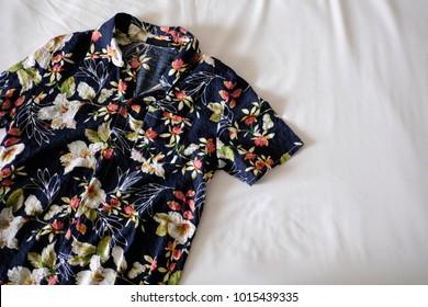 Hawaiian shirt is placed on a white mattress