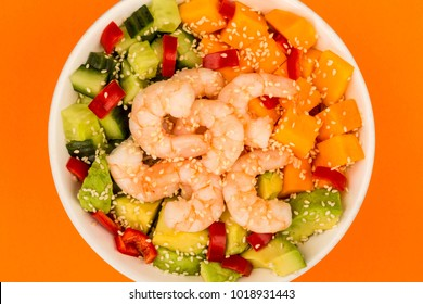 Hawaiian Shrimp or Prawn Poke Bowl With Sweet Potatoes Avocado And Cucumber Against An Orange Background