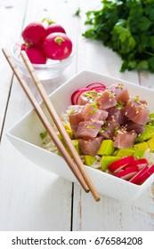 Hawaiian tuna poke bowl with avocado, radishes and sesame seeds on white wooden background