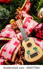 Hawaiian ukulele and large ribbon on Christmas tree.