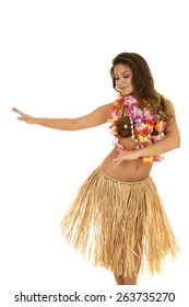 A Hawaiian woman dancing in her grass skirt and coconut bra.