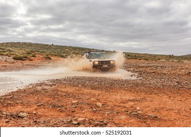 Hawker, Flinders Ranges, South Australia, december 26, 2011: A Toyota Land cruiser moving at high speed over a plateau by a Creek so that the water spray high and the car is covered with water and mud
