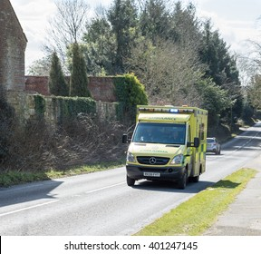 HAWKHURST,KENT,UK - MARCH 25 2016 : An Ambulance on an emergency call out races along a road with its sirens on and blue lights flashing