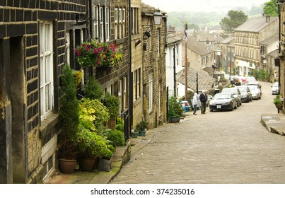 HAWORTH, ENGLAND - June, 2013: Old narrow street with tourists in the village of Haworth in summer day