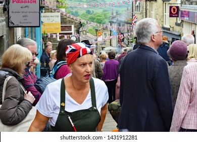 Haworth, West Yorkshire, UK. May 18, 2019. Main street of Haworth during 1940s weekend with crowd of people and reenactor with union flag scarf